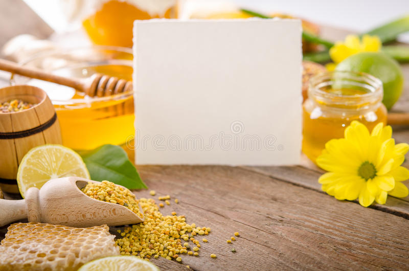 Beekeeping products with lemons on a wooden table. With empty card for you text . side view royalty free stock photography