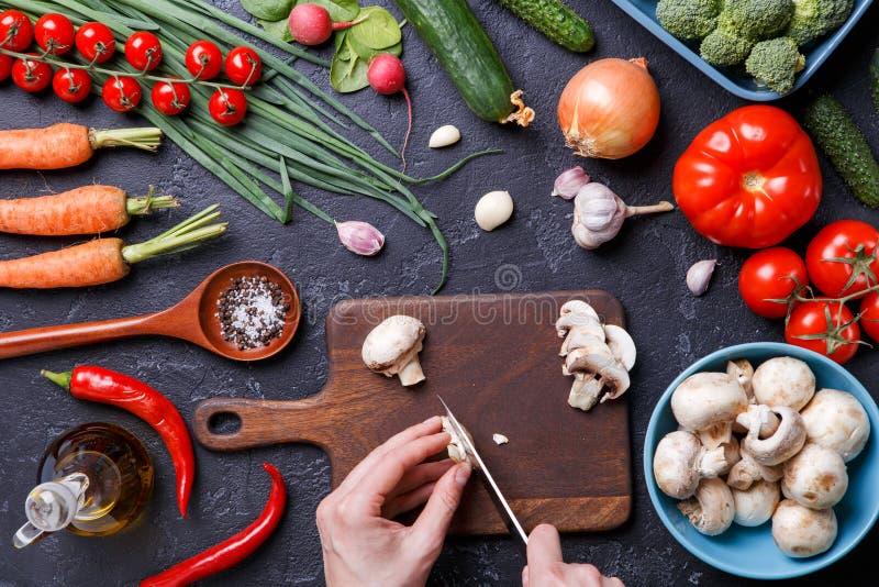 Beeld bovenop verse groenten, paddestoelen, scherpe raad, olie, mes, handen van kok stock afbeeldingen