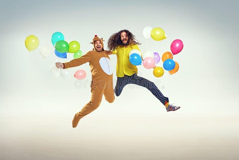 Beeld die twee grappige kerels voorstellen die en ballons springen houden stock afbeeldingen