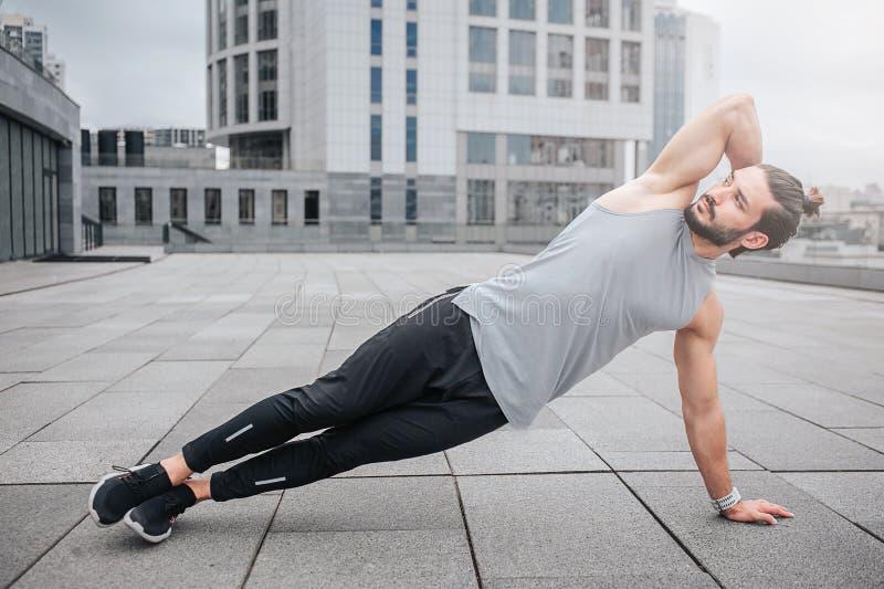 Beeld die van de goed-bilt-put jonge mens zijn lichaam uitrekken door oefeningen te doen Hij houdt één hand achter hoofd De kerel royalty-vrije stock foto