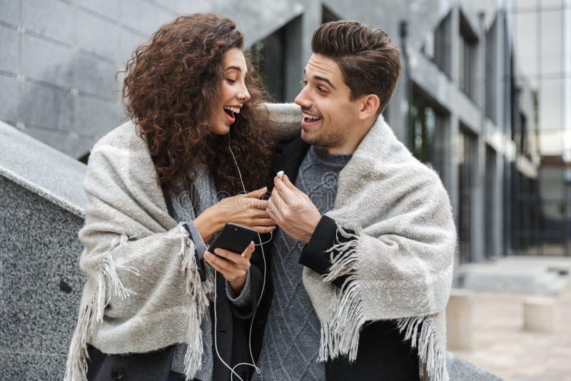 Beeld die van de Kaukasische paarmens en vrouw die oortelefoons dragen, aan muziek luisteren samen terwijl status over de grijze  stock afbeeldingen