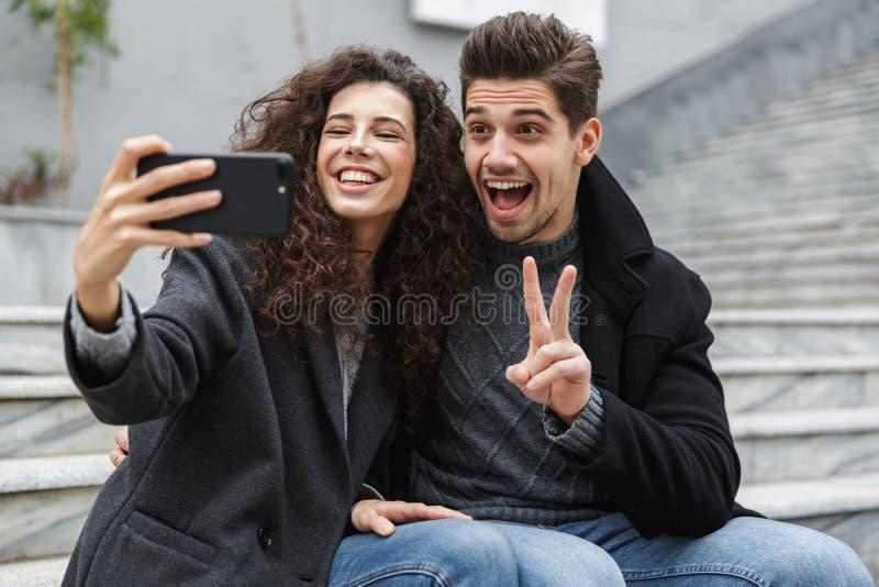 Beeld die van donkerbruine van de paarman en vrouw jaren '20 in warme kleren, selfie foto op celtelefoon nemen terwijl het zitten stock foto's