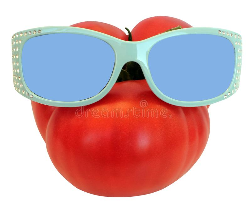 Beeld die van een rode grote tomaat, zonnebril, goed die de zomergewas de landbouwconcept dragen, op witte achtergrond wordt geïs royalty-vrije stock fotografie
