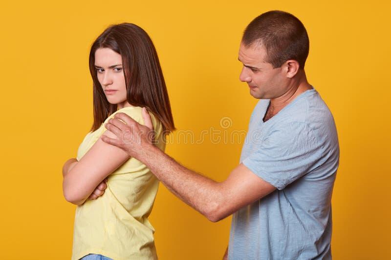 Beeld die van het quilty echtgenoot proberen om haar vrouwenrust te houden, verontschuldigen, zich wat betreft haar schouder met  stock foto