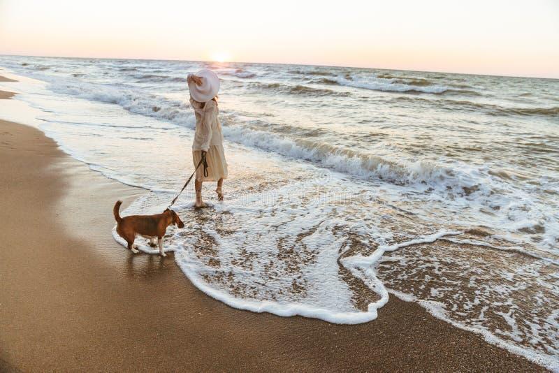 Beeld die van Kaukasische vrouwenjaren '20 in de hoed van het de zomerstro, door kust met haar hond lopen royalty-vrije stock foto's