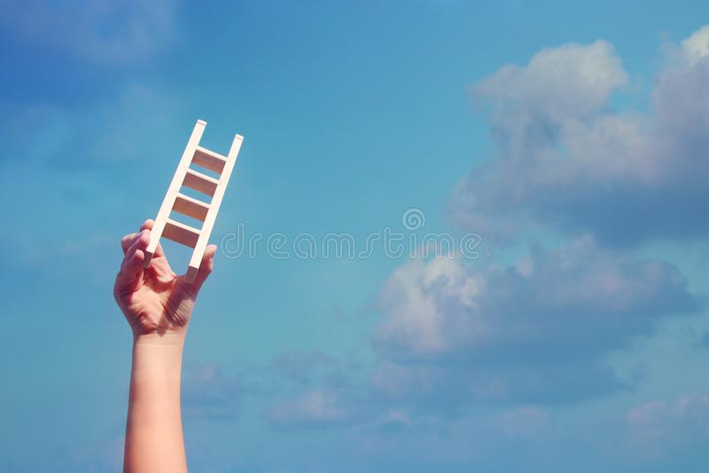 Beeld die van kindhand een ladder houden tegen de hemel Onderwijs en succesconcept stock afbeeldingen