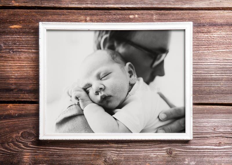 Beeld die van vader zijn baby houden Houten achtergrond royalty-vrije stock fotografie
