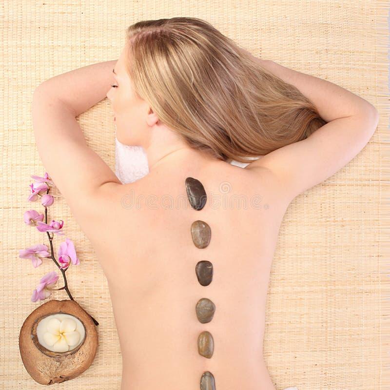 Beeld die van vrouw in kuuroordsalon op het massagebureau liggen royalty-vrije stock afbeelding