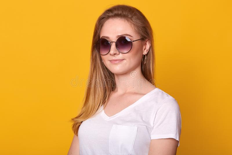 Beeld die van zoete zekere jonge dame die zich over heldere gele achtergrond in studio bevinden, witte toevallige t-shirt dragen  royalty-vrije stock afbeelding