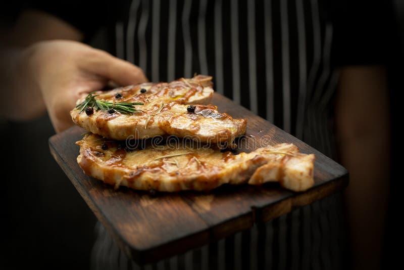 Beeld het koken op keuken Het hoofdlapje vlees van de Chef-kokholding Vrouwenchef-kok royalty-vrije stock fotografie