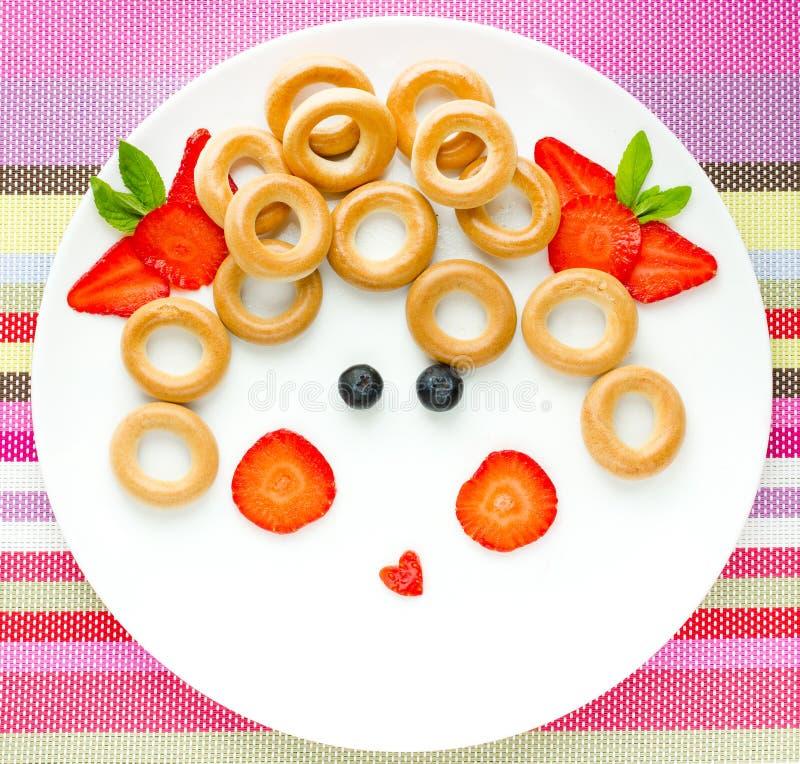 Beeld op een plaat - meisjesgezicht van ongezuurde broodjes met fruit en berrie stock foto's
