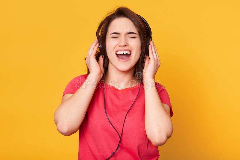 Beeld van aantrekkelijk energiek brunette die toevallige rode t-shirt dragen, die hoofdtelefoons hebben, luisterend aan muziek, h stock foto's