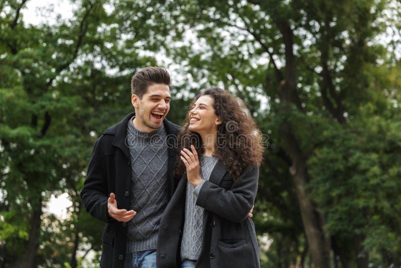 Beeld van aantrekkelijke van de paarman en vrouw jaren '20 die, en door groen park lopen koesteren stock foto