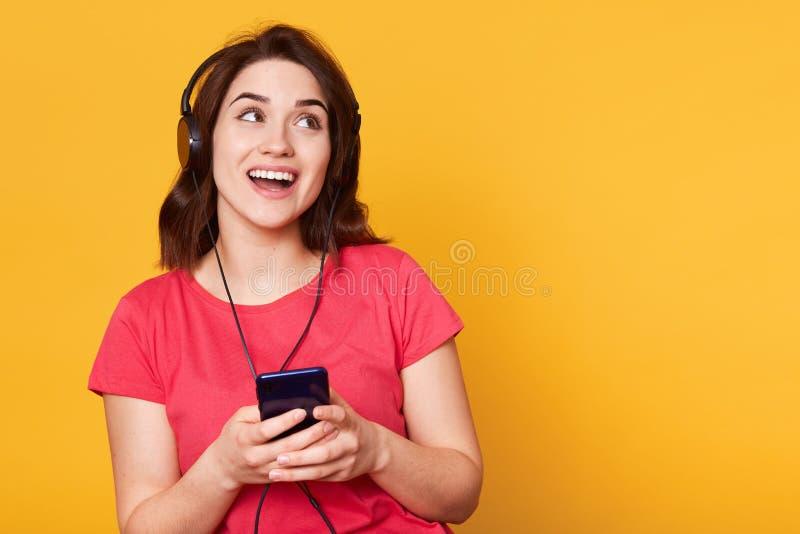 Beeld van aantrekkelijke Europese vrouwenbewaarcel telefoon en het luisteren aan muziek via oortelefoons, wijfje die opzij glimla stock fotografie
