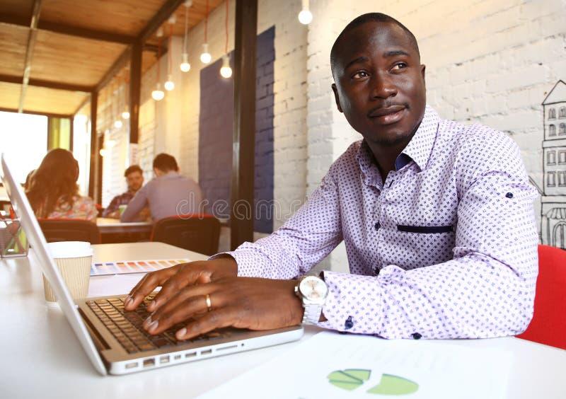 Beeld van Afrikaanse Amerikaanse zakenman die aan zijn laptop werken Knappe jonge mens bij zijn bureau royalty-vrije stock afbeelding