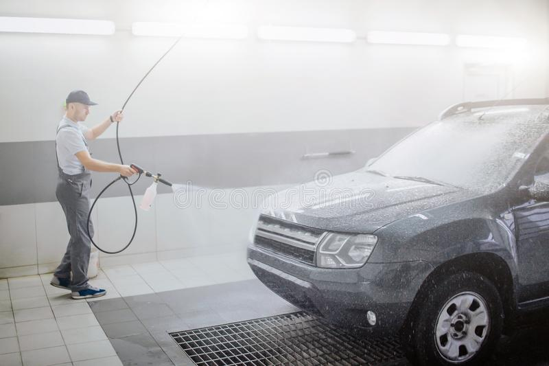 Beeld van arbeiders schoonmakende auto Hij gebruikt waternevel FO dat De jonge mens houdt flexibele slang Hij is ernstig en royalty-vrije stock fotografie