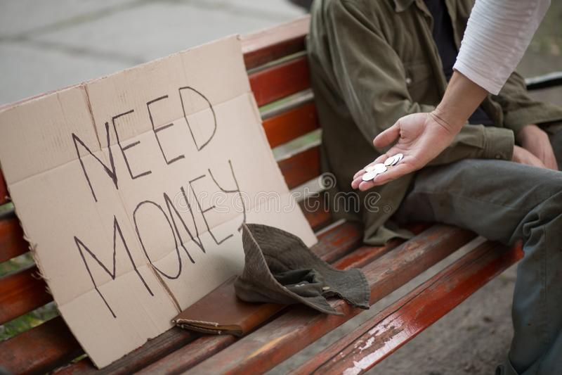 Beeld van bank met karton met het geld, de hoed en de hand van de tekenbehoefte met muntstukken stock foto