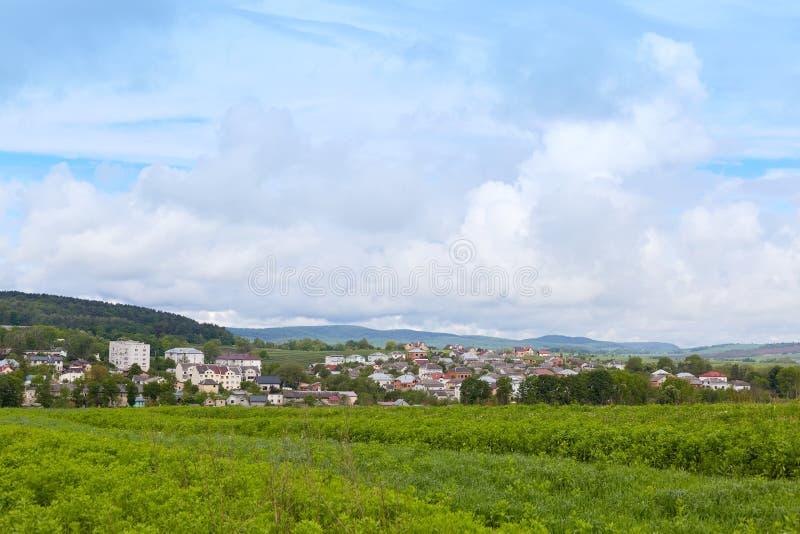 Beeld van beste plaats van wereld, dorp in bergen, foto van aard scenary, blauwe hemel met wolken, groen gras en vele huizen  royalty-vrije stock foto