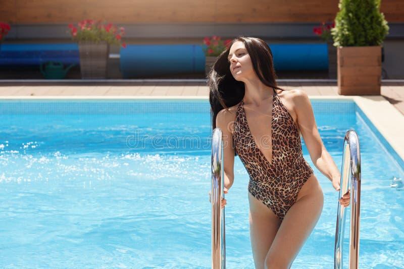 Beeld van bevallige aantrekkelijke slanke dame die uit zwembad komen, die op strakke leuningen houden, hebbend de zomerrust bij k stock afbeelding