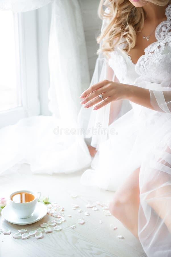 Beeld van charmante blondehand die aan kop thee trekken royalty-vrije stock foto's