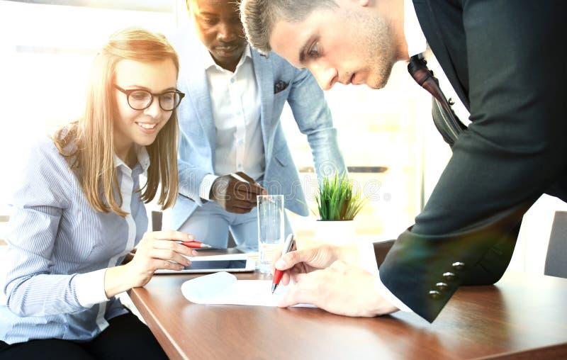 Beeld van commerciële teamzitting bij de lijst en het bespreken van een nieuw project stock afbeelding