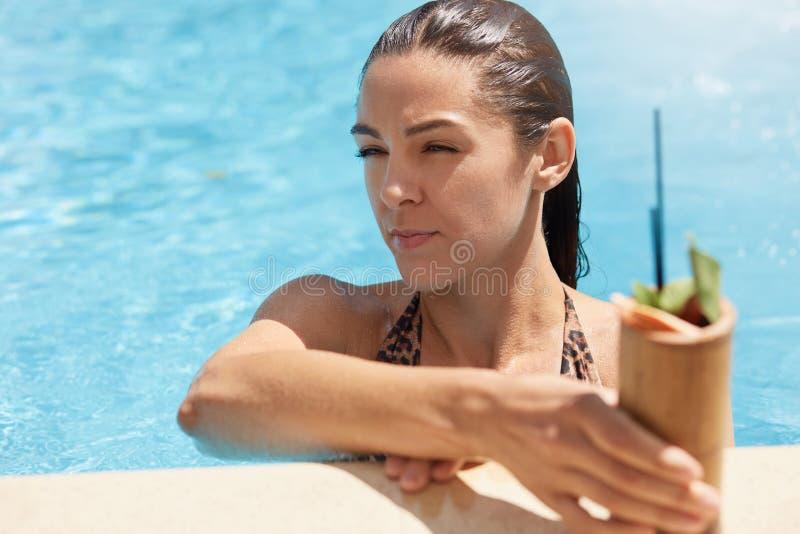 Beeld van dame met ernstige gelaatsuitdrukking die verse cocktail in zwembad en het ontspannen drinken Mooi wijfje die rust hebbe royalty-vrije stock fotografie