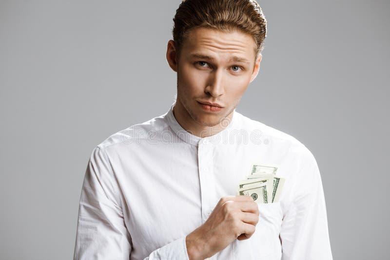 Beeld van de aantrekkelijke Kaukasische mens met geld in een zak royalty-vrije stock afbeeldingen