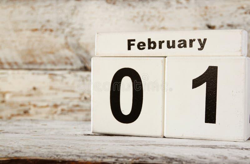 Beeld van de Eerste houten uitstekende kalender van Februari op witte achtergrond stock afbeeldingen