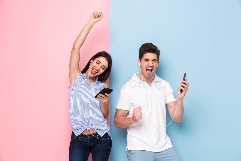 Beeld van de gelukkige mens en vrouw die oortelefoons dragen die aan musi luisteren royalty-vrije stock afbeelding