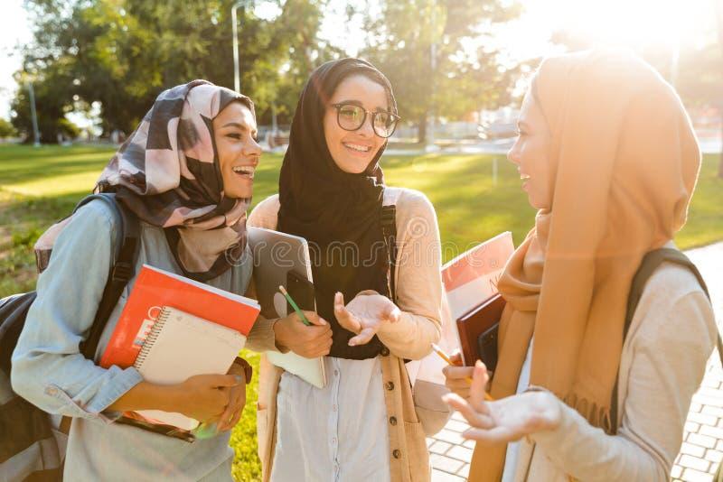 Beeld van de gelukkige vrouwen die van vrienden moslimzusters in openlucht het houden van boeken lopen stock afbeelding