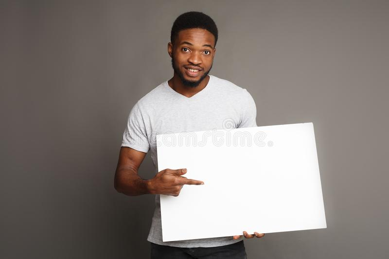 Beeld van de jonge Afrikaans-Amerikaanse mens die witte lege raad houden stock foto's