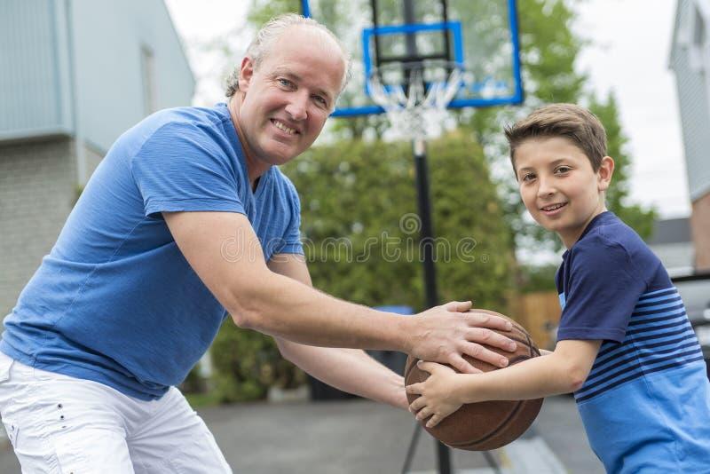 Beeld van de jonge mens en zijn zoons speelbasketbal royalty-vrije stock foto's