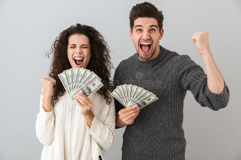 Beeld van de knappe mens en de mooie die ventilator van de vrouwenholding van dollargeld, over grijze achtergrond wordt geïsoleer royalty-vrije stock afbeeldingen