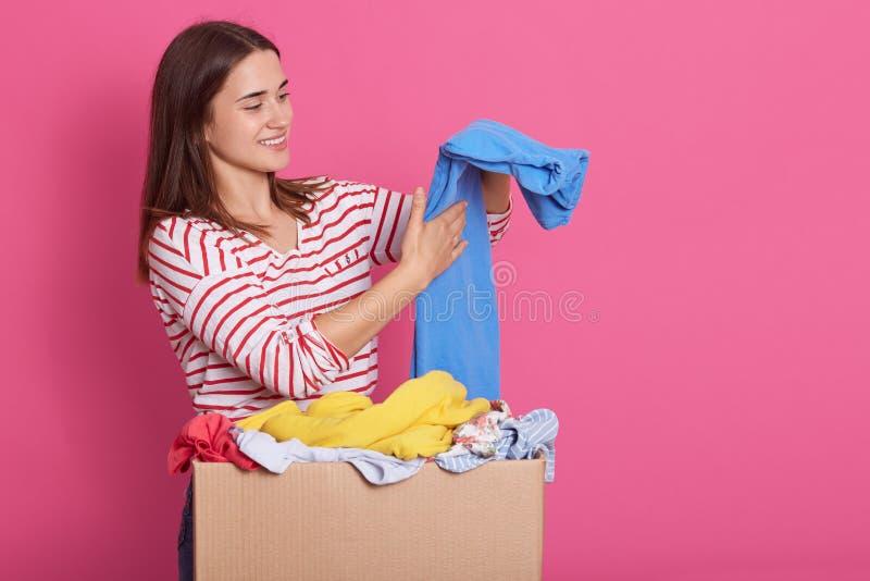 Beeld van donkerbruine aantrekkelijke dame die, oprecht glimlachend, zettend geschonken kleren in orde, die blauwe broeken binnen stock foto's