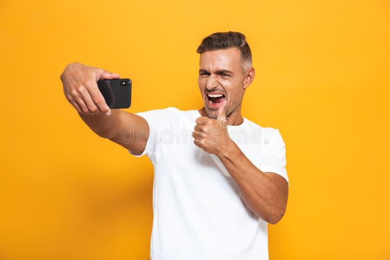 Beeld van donkerbruine mensenjaren '30 in witte t-shirt die en selfie foto op mobiele telefoon glimlachen nemen royalty-vrije stock afbeelding