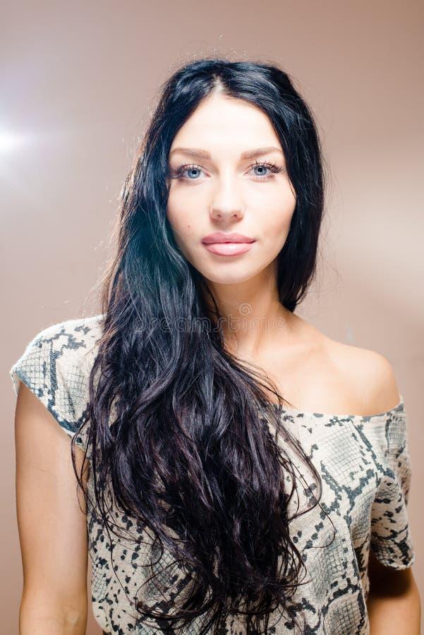 Beeld van donkerbruine mooie vrouw met de lange zwarte schitterende lippen van haar blauwe ogen mollige blote schouder die zacht g stock fotografie