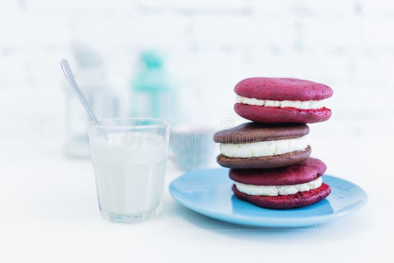 Beeld van drie whoopiepastei of maanpastei met glas van melk en lepel stock afbeeldingen