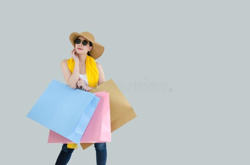 Beeld van een gelukkige jonge Chinese vrouw in wit de zomeronderhemd, sjaal en jeans die zonnebril dragen die met het winkelen za royalty-vrije stock fotografie