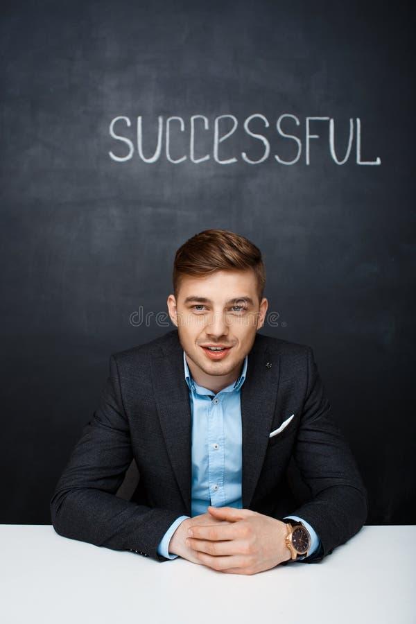 Beeld van een gelukkige sprekende mens over zwarte raad met tekst succ royalty-vrije stock foto
