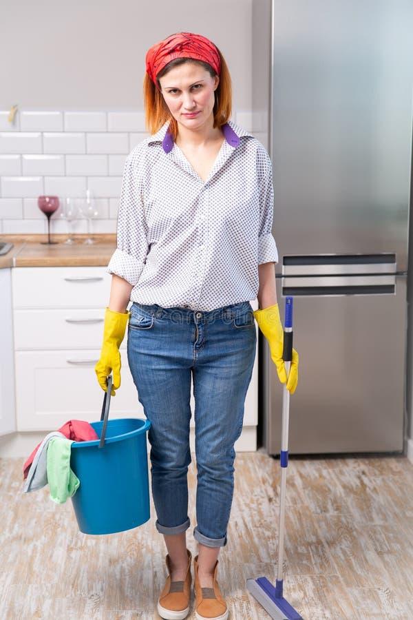 Beeld van een huisvrouw die in beschermende handschoenen een vlakke nat-zwabber en een emmer met vodden houden terwijl het schoon royalty-vrije stock foto's