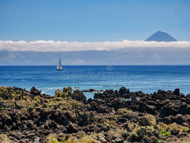 Beeld van een klip met een varende boot in de Atlantische Oceaan en het Eiland Pico met berg Pico op de achtergrond royalty-vrije stock fotografie