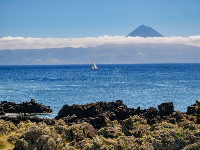 Beeld van een klip met een varende boot in de Atlantische Oceaan en het Eiland Pico met berg Pico op de achtergrond royalty-vrije stock afbeeldingen