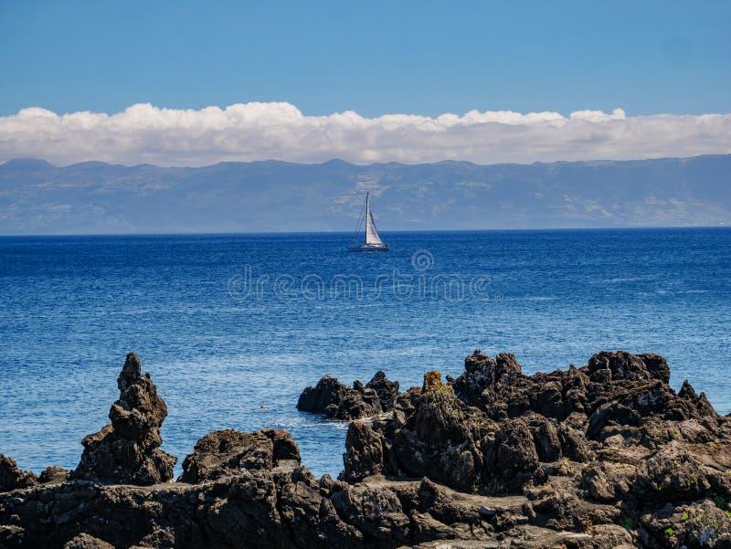 Beeld van een klip met een varende boot in de Atlantische Oceaan en het Eiland Pico met berg Pico op de achtergrond stock afbeeldingen