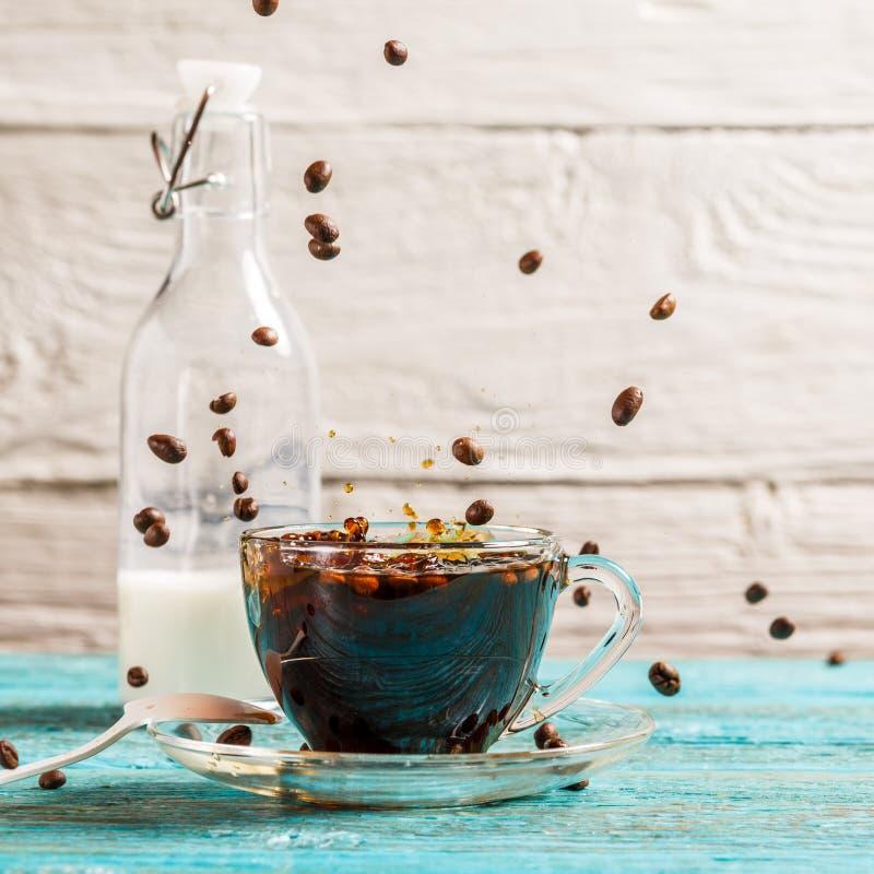 Beeld van een kop van koffie, een kruik melk met dalende koffiebonen stock afbeeldingen