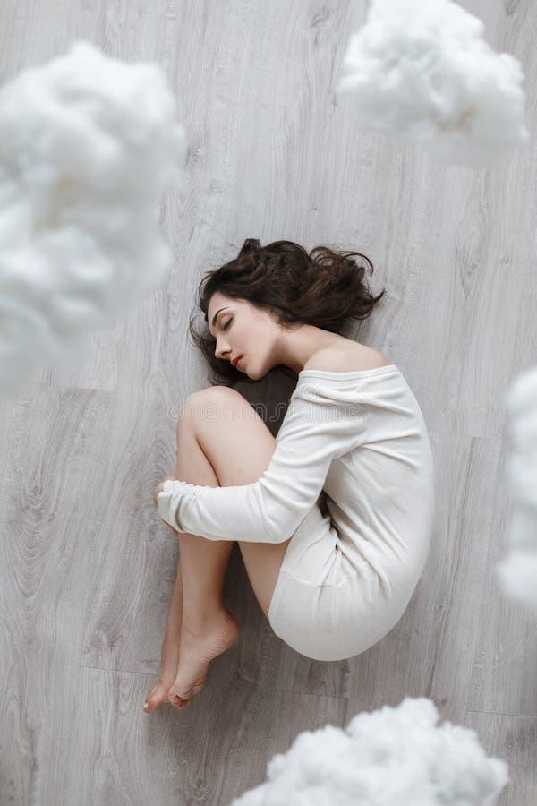 Beeld van een meisje die op de vloer in de wolken liggen stock foto