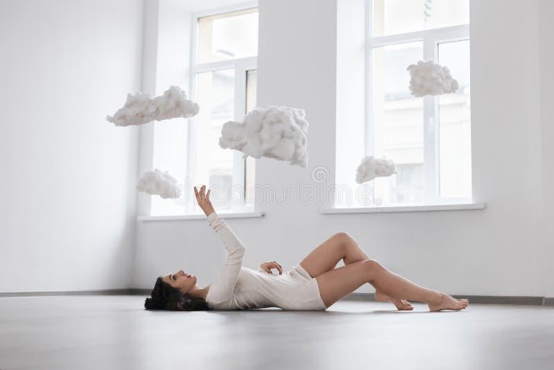 Beeld van een meisje die op de vloer liggen die voor de wolken bereiken royalty-vrije stock afbeelding