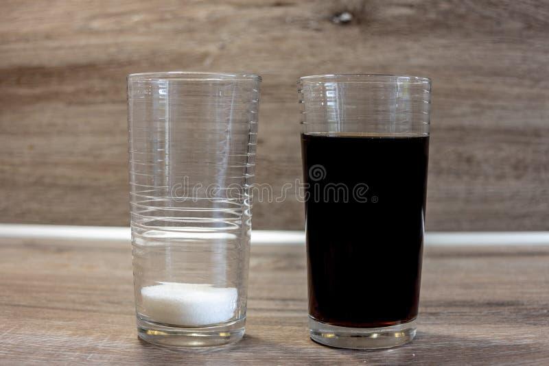 Beeld van een 200ml-glas kola en een 2de glas met de hoeveelheid suiker daarin royalty-vrije stock fotografie