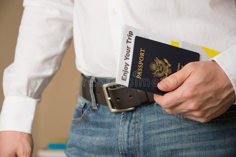 Beeld van een personenhand die Amerikaans paspoort houden en klaar te reizen stock foto
