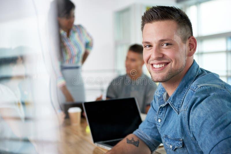 Beeld van een succesvolle toevallige bedrijfsmens die laptop met behulp van tijdens vergadering royalty-vrije stock fotografie