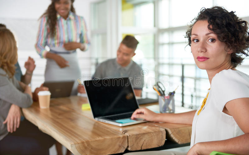 Beeld van een succesvolle toevallige bedrijfsvrouw die laptop met behulp van tijdens vergadering stock fotografie